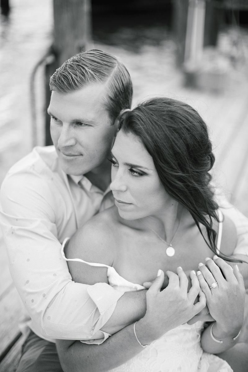 black and white couple holding each other looking off of a dock
