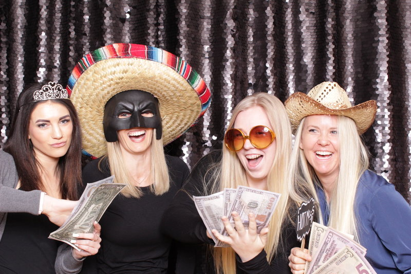 Ladies have a fun time taking photo booth pics with silly props