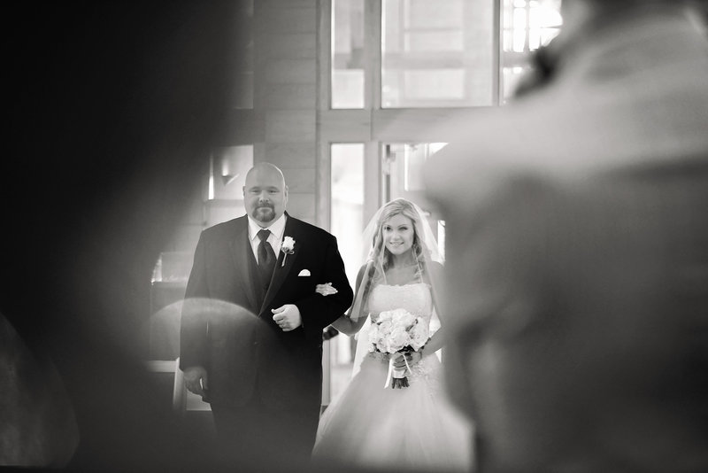 black and white photo of bride and her father walking down the aisle
