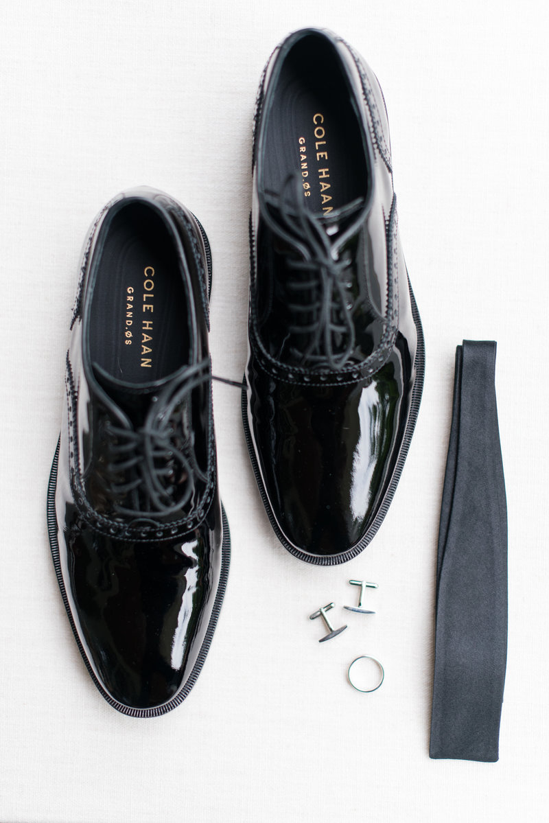 detail shot of a black tie wedding with black shiny shoes and cuff links