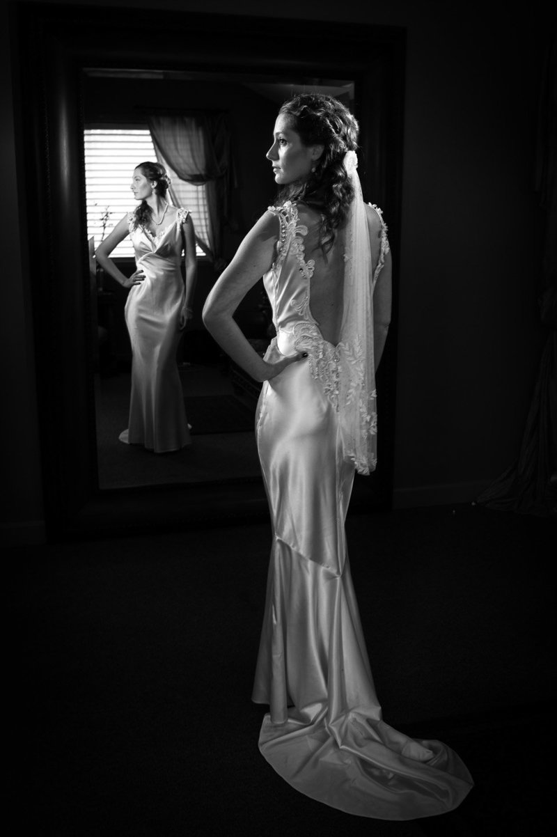 A black and white portrait of a destination wedding bride in front of the big mirror at Eagle Crest Resort by Pete Erickson Photography.