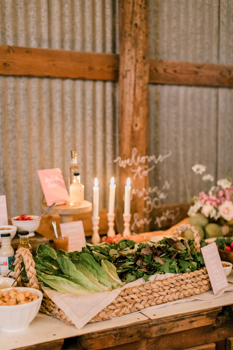 wedding reception table set up with food in basket and candles