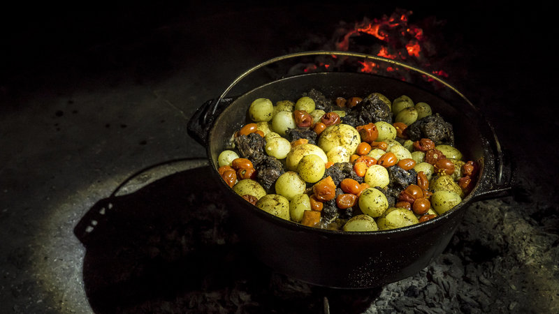 Cooking Ox tail in a ductch oven over open flames in Namibia with Raven 6 Studios and Omujeve Safaris