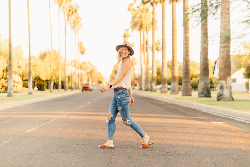 Joelle smiles while walking across a palm tree-lined street while talking about the Behind the Scenes of Scaling My Business on The Jo Show Podcast
