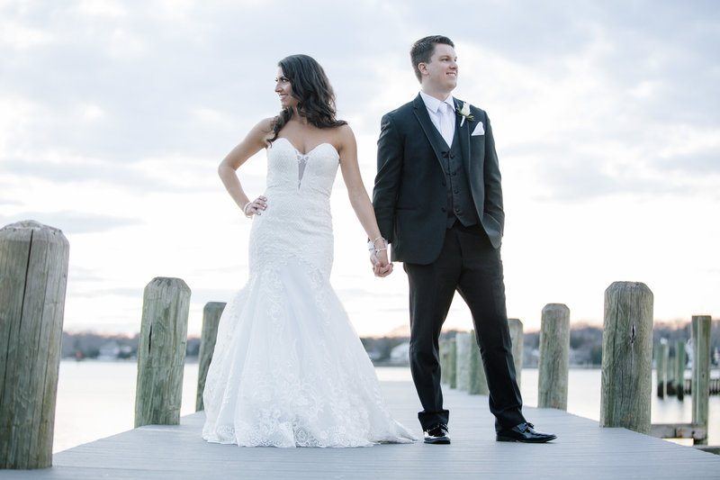bride and groom holding hands on dock