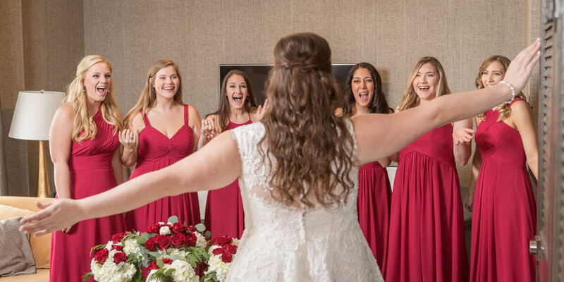 The bride reveals her dress to her bridesmaids on her wedding day.