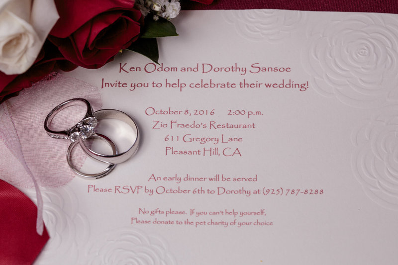 Photo of wedding invite and rings
