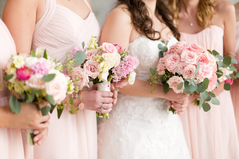 Bride and bridesmaids hold pink peony bouquets
