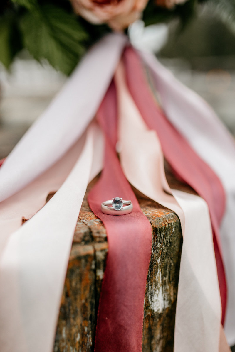 Engagement ring and wedding band on tree stump with ribbons