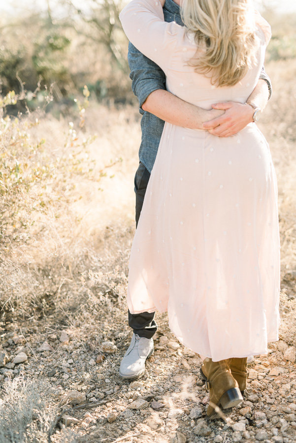 Tucson Desert Engagement Session Photo of Couple Hugging at Gates Pass During Golden Hour | Tucson Wedding Photographer