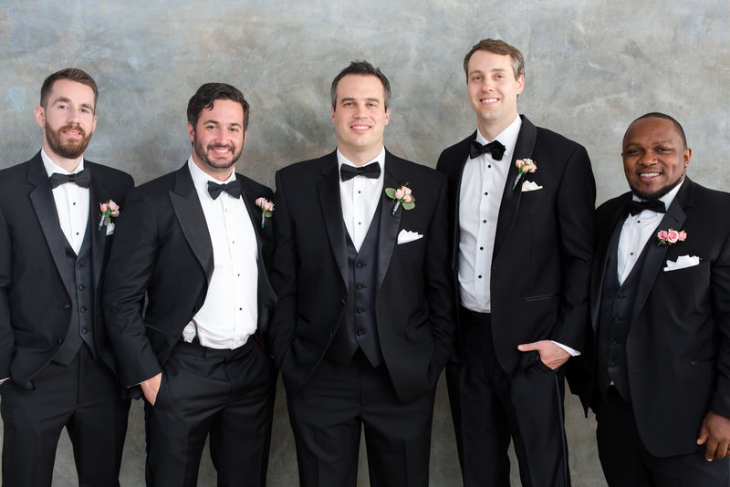Groom and groomsmen stand together in black tuxedos
