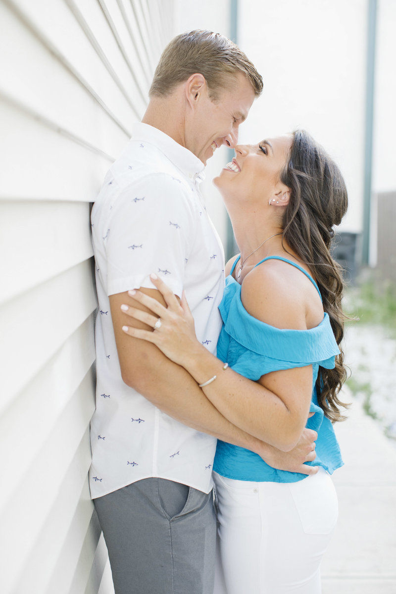 smiling couple leaning against white wall