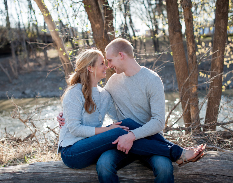 Spring engagement photos in Fargo by Kris Kandel. The red river in the background and leaves just budding.