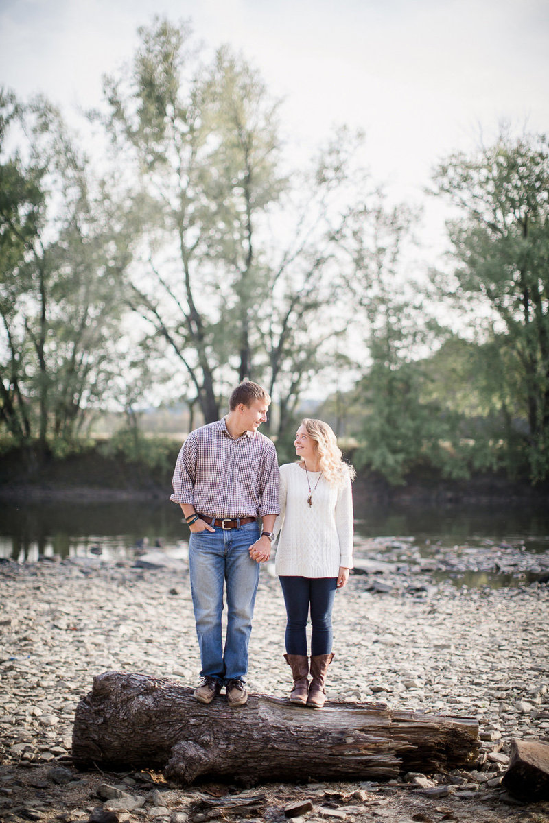 Standing on a log with river behind them by Knoxville Wedding Photographer, Amanda May Photos.