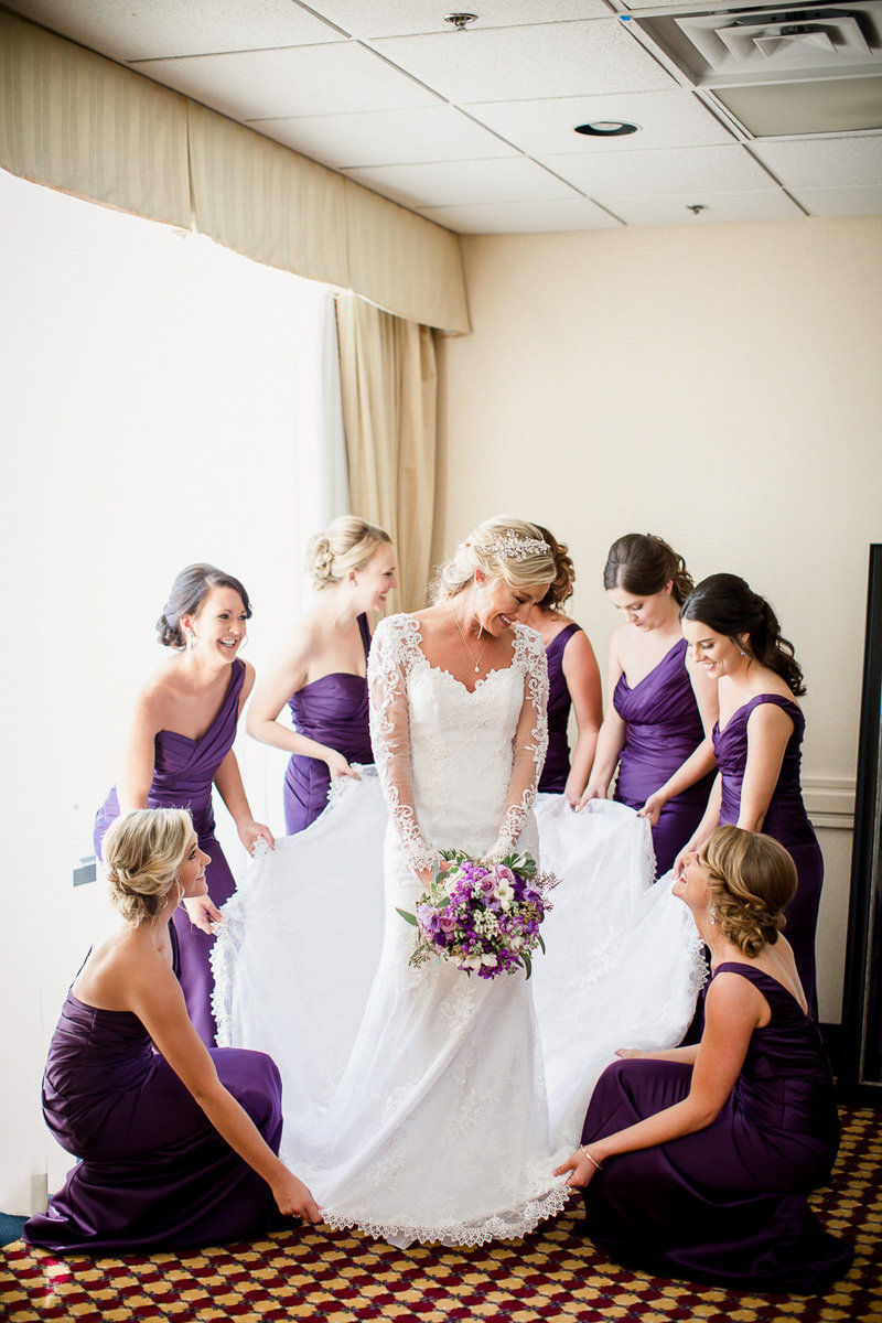 Bridesmaids help bride get dressed at downtown Knoxville Marriott by Knoxville Wedding Photographer, Amanda May Photos.