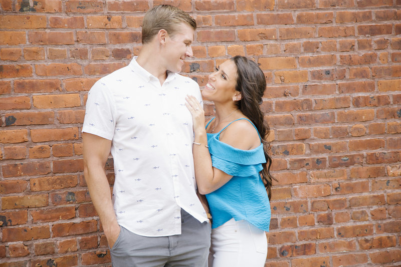 couple looking at each other in summer in front of brick wall