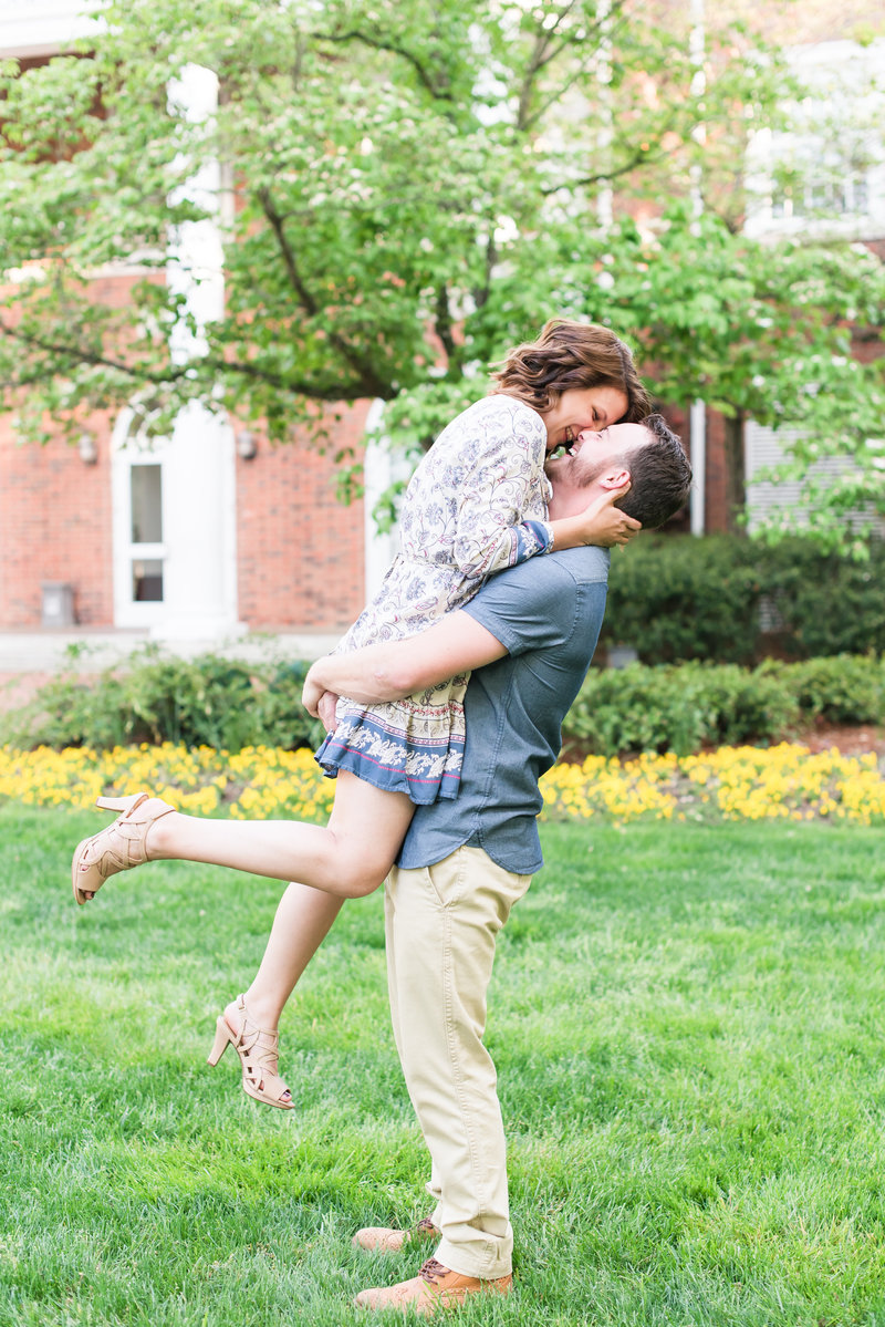 young man lifting up young lady while laughing in gardens at Elon College