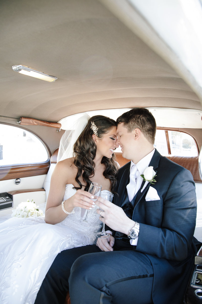 bride and groom inside rolls-royce cheers