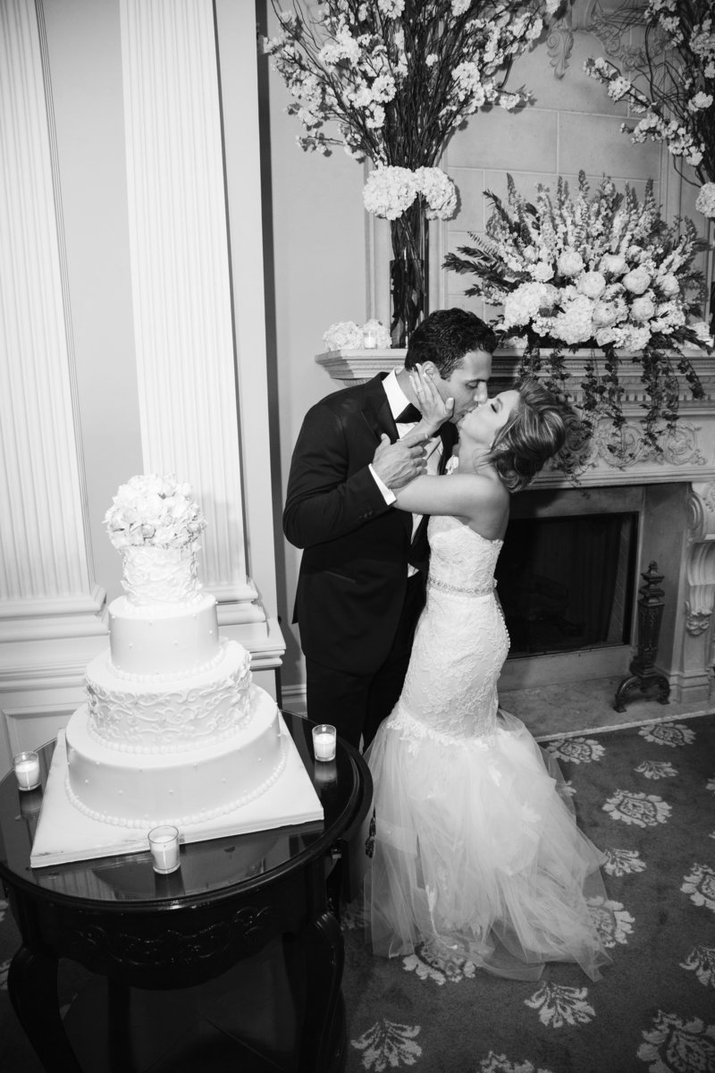 bride and groom kiss at cake cutting  at park savoy