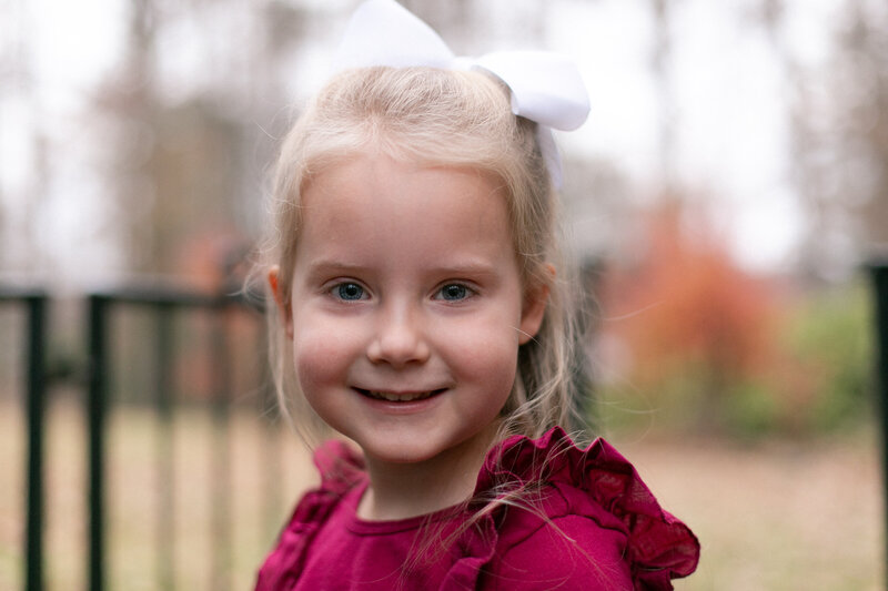 4 year old girl with burgundy shirt and white bow smiling at camera