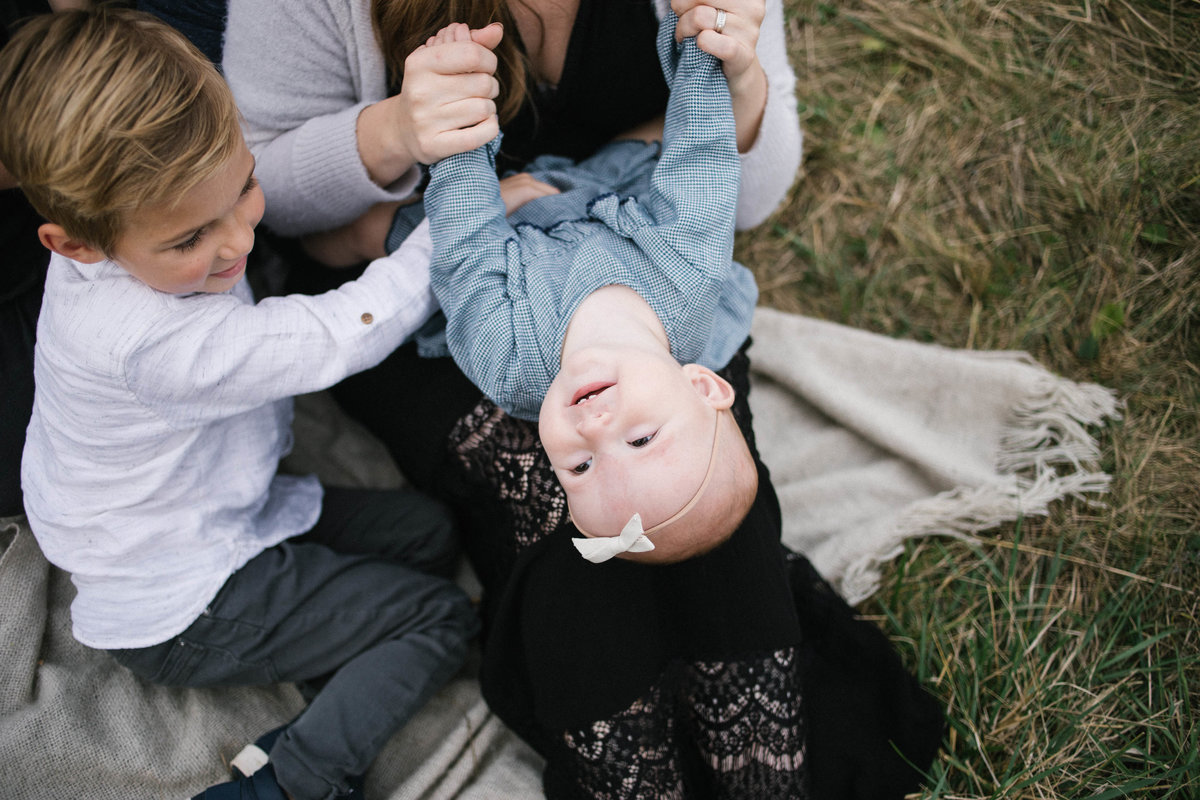 Mother and son tickling baby sister during family session with Elle Baker Photography