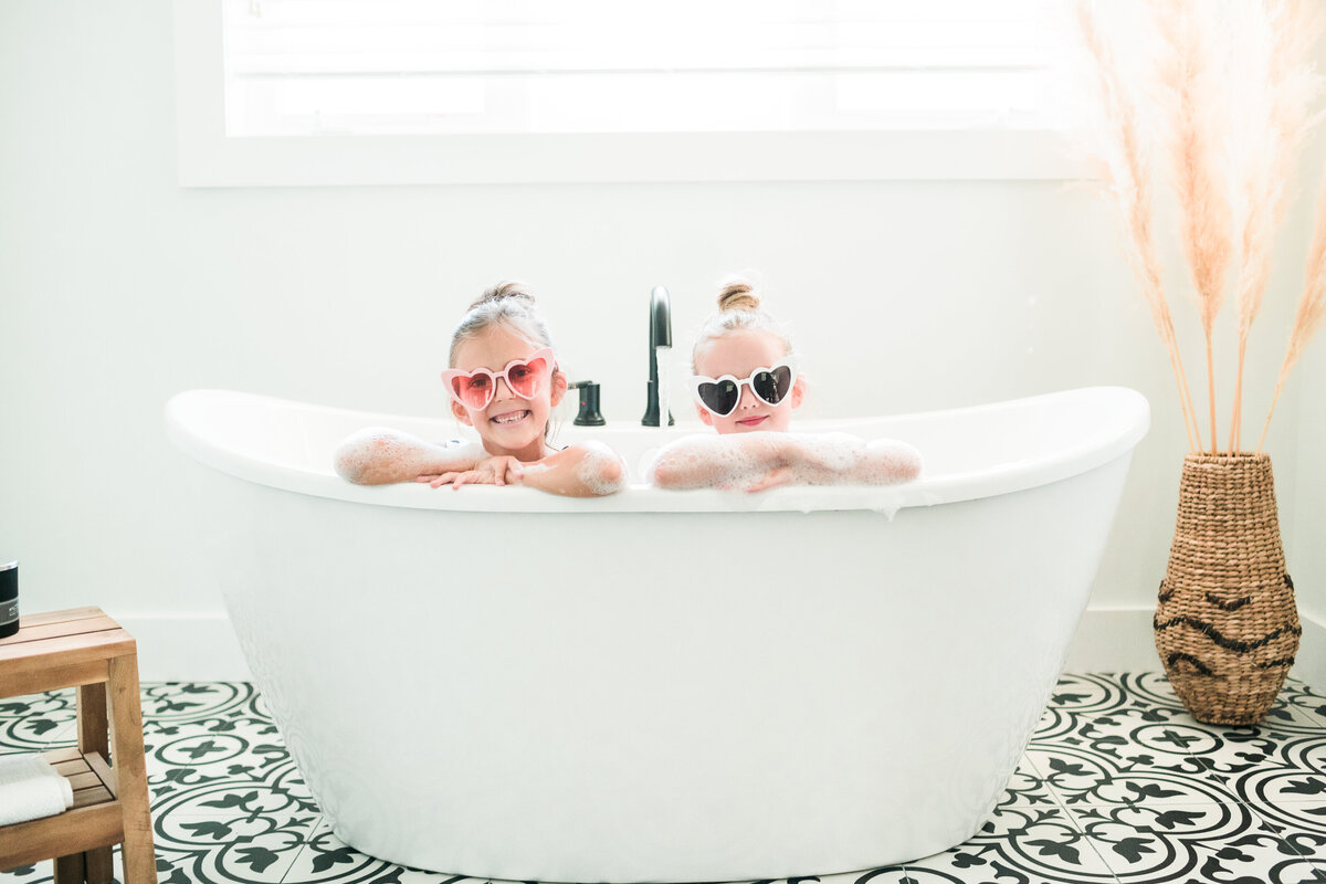 two young girls in a bathtub wearing sunglasses