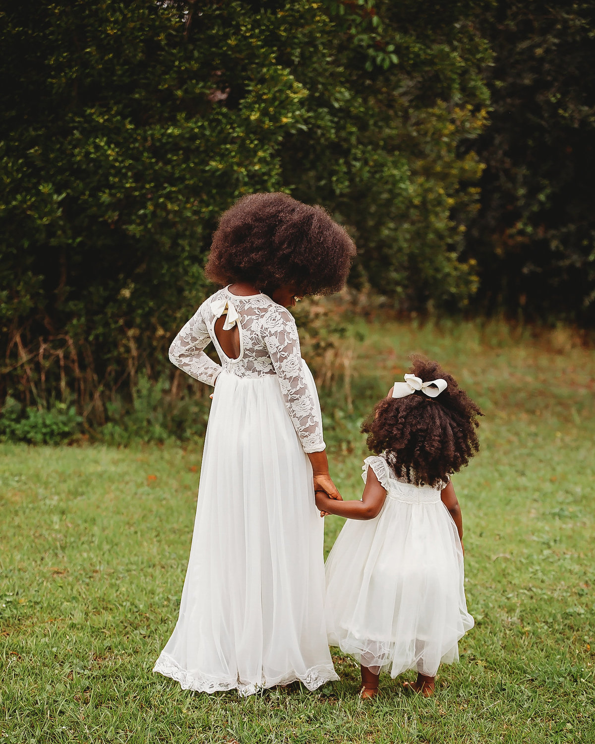 Sisters walk in white dresses, stop and look at each other