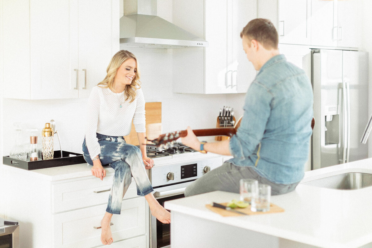 blonde woman sitting on white kitchen counter smiling at man playing guitar across from her