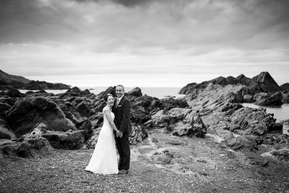 Black and white wedding photo of couple on beach at Tunnels Beaches