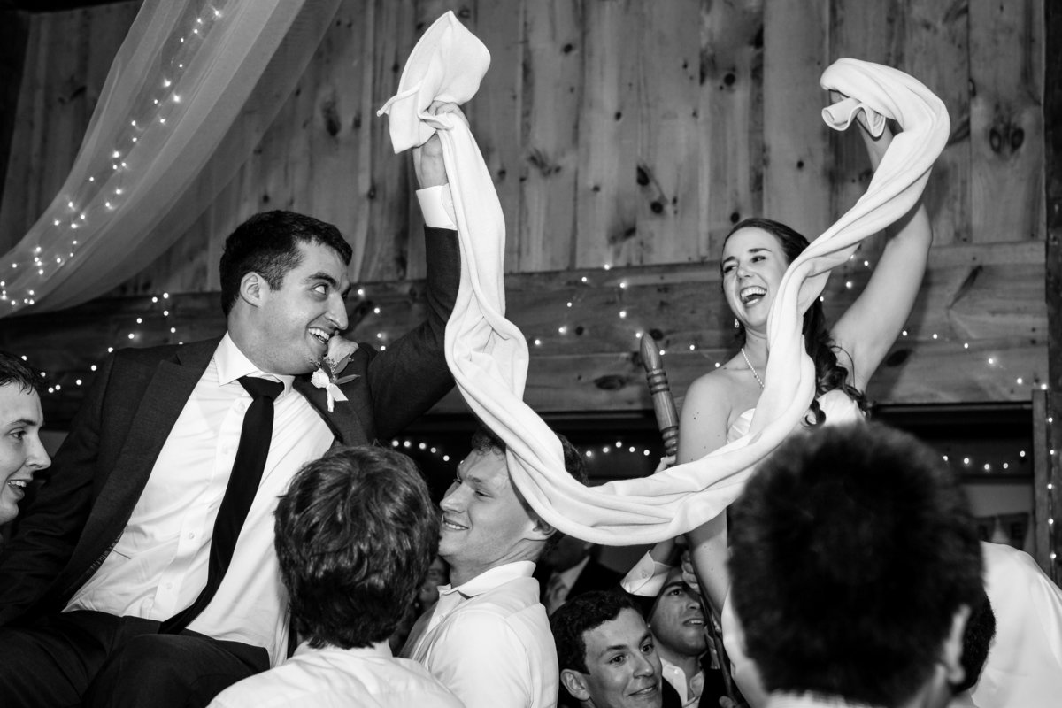 The bride and groom are celebrated with the horah dance at their reception at Clarks Cove Farm in Maine