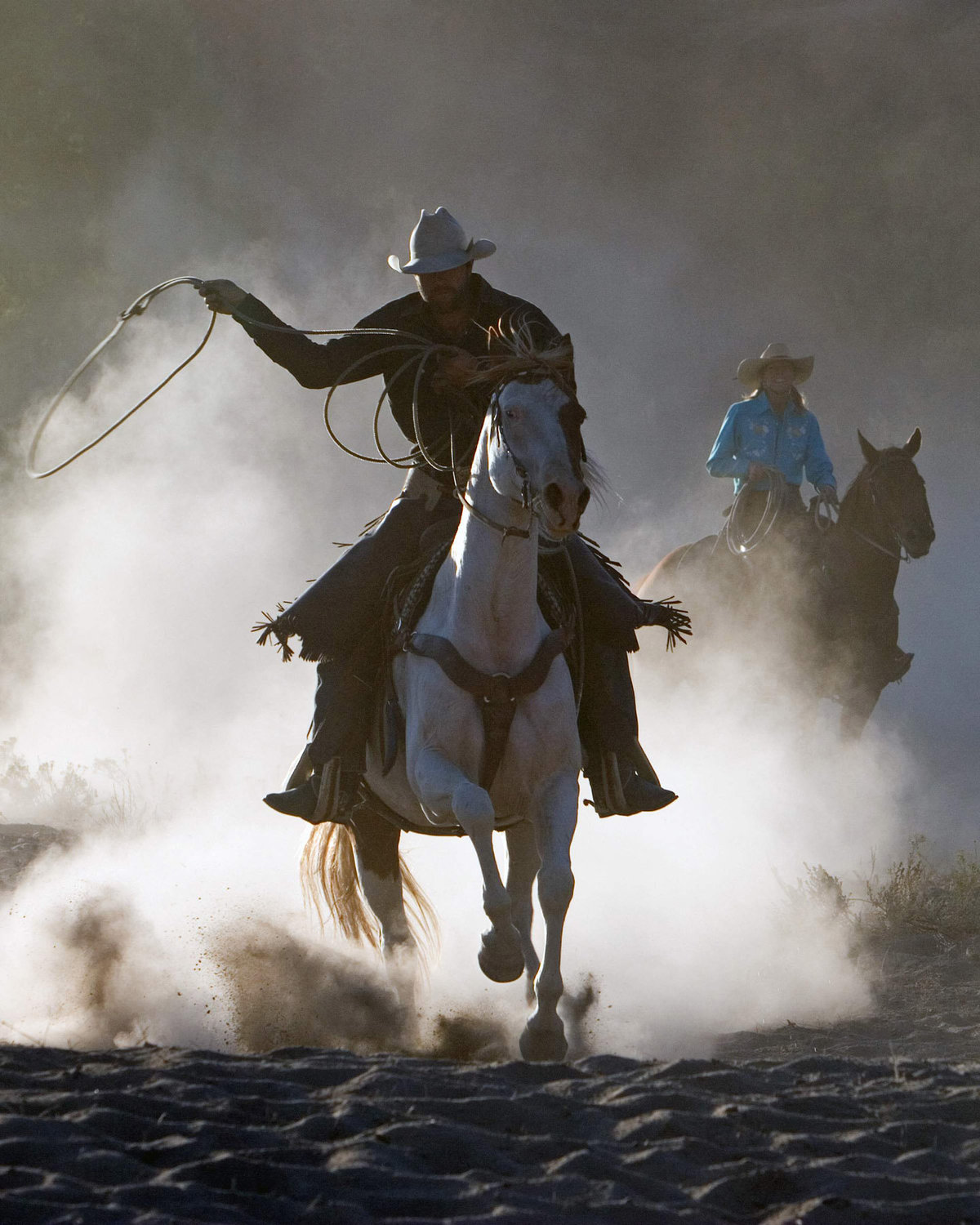 cowboy running in dust Lynette Smith Photography