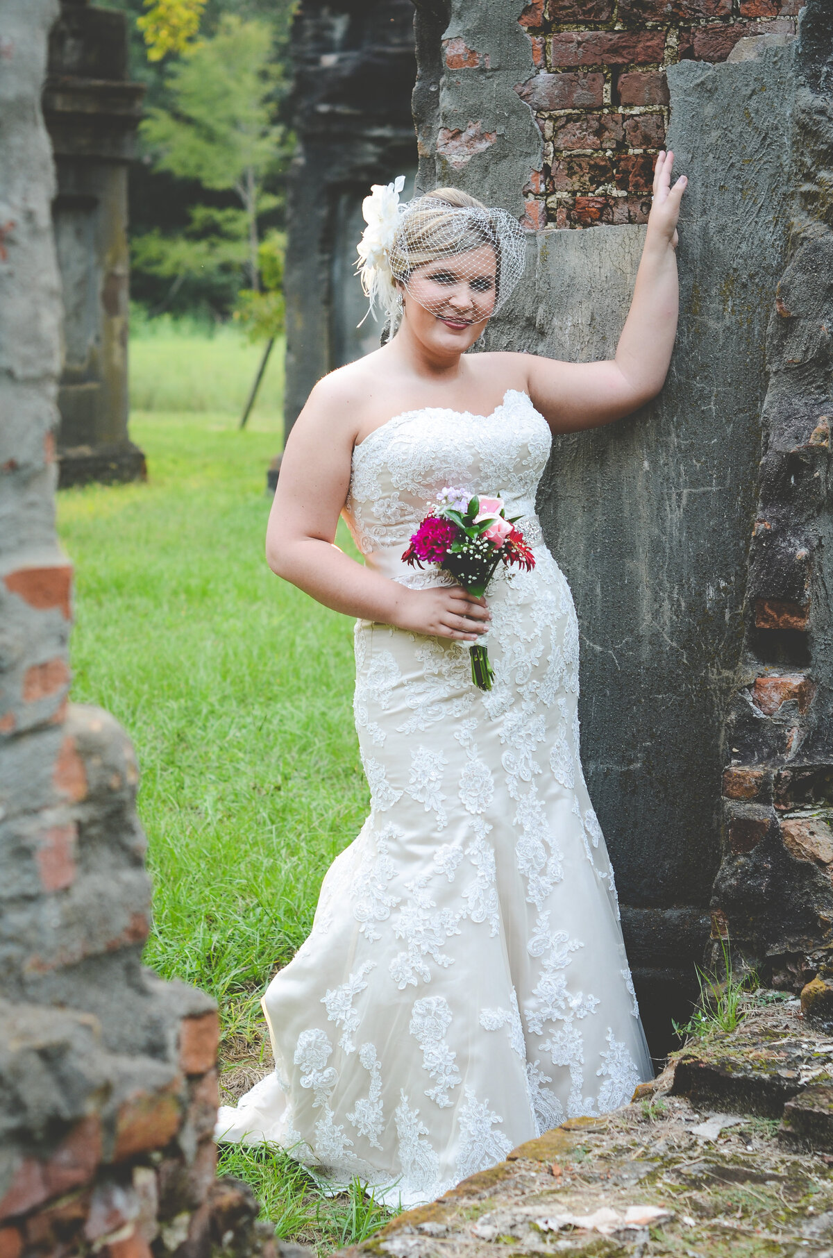 Beautiful bridal portrait photography: bride with birdcage veil stands among the ruins of Windsor Plantation in Mississippi