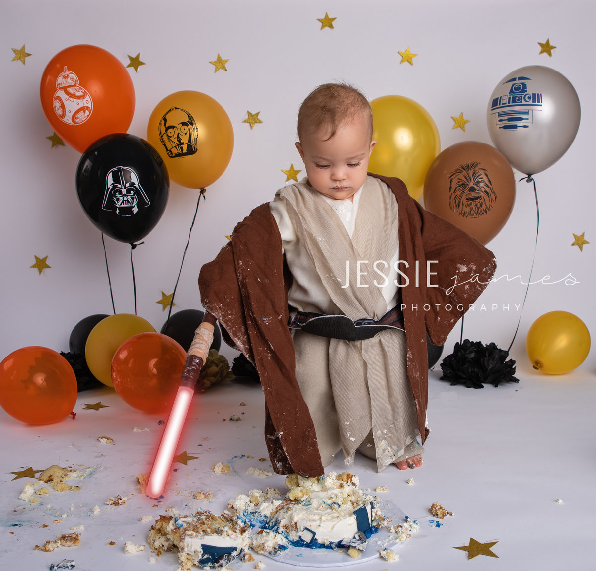 one year old girl star wars themed photo, baby is holding lightsaber and smashing her cake