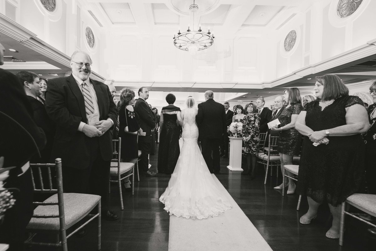 Bride walking down the aisle with her parents at Watermill Caterers