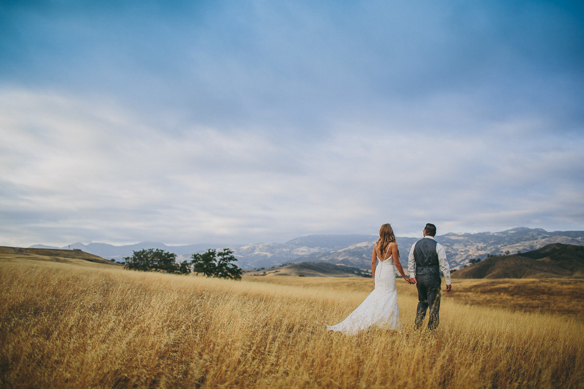 Bride & groom hold hands as they walk in the hills of Solvang after their Solvang wedding.