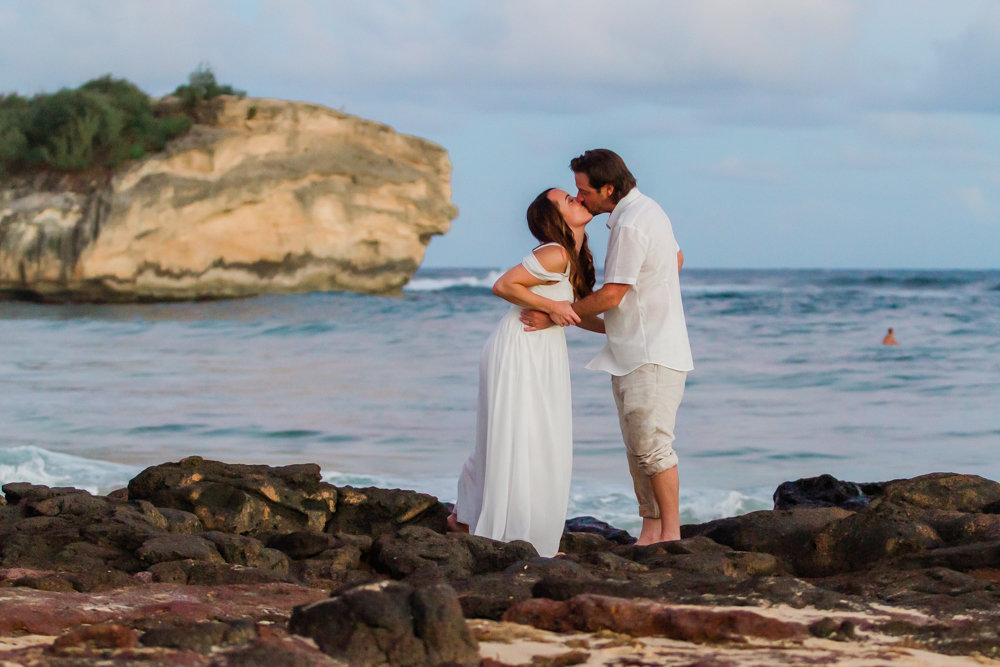 wedding couple kissing on rocks with ocean and cliff in background