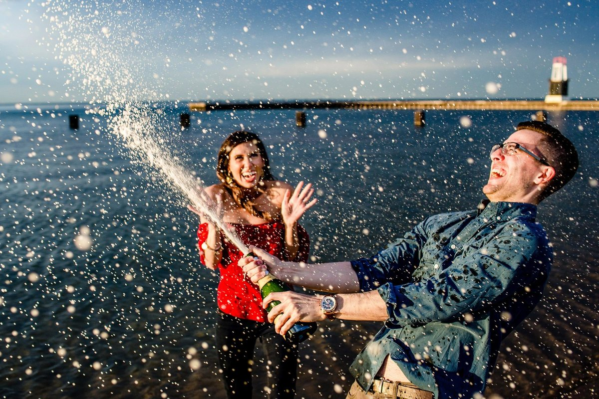 A couple sprays champagne during a North Avenue beach engagement session.