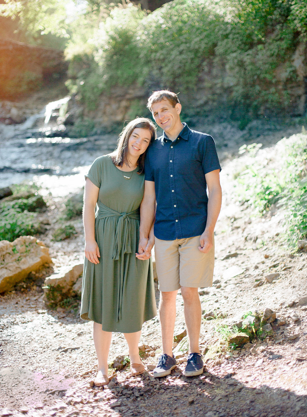 willow river state park waterfall background as couple stands hand in hand