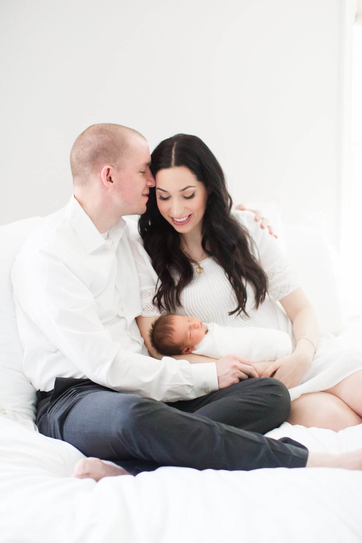 Couple holding newborn baby sitting on white bed