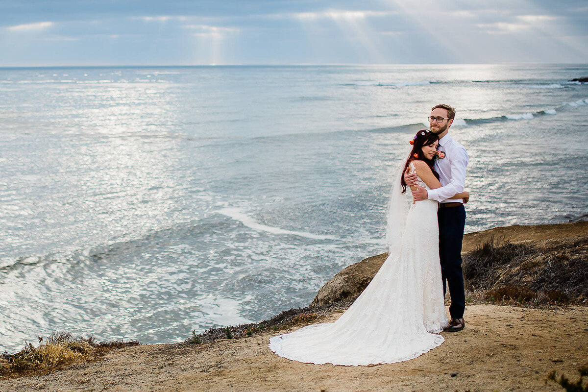 bride and groom on san diego cliff