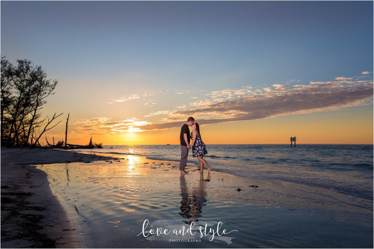 Beer Can Island Engagement Photo of couple kissing by the water at sunset