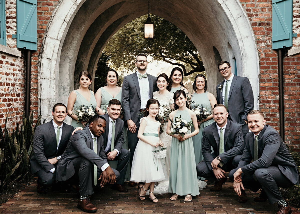 A photograph of the bride and groom standing with their wedding party, smiling together outdoors under a vintage archway on a brick walk