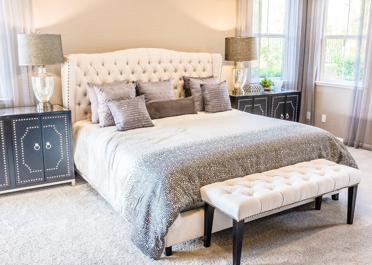 A luxurious bed with a padded headboard has two units with studs. and glass lamps and a bench at the foot of the bed.