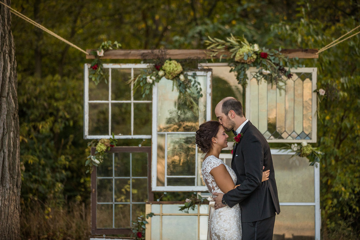 groom kissing bride with vintage windows for decor