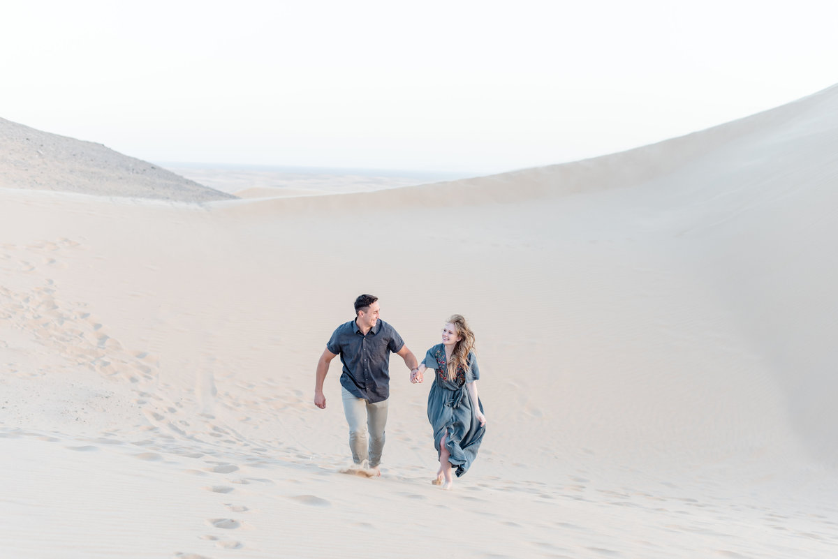 couple holds hands and runs towards camera at glamis sand dunes
