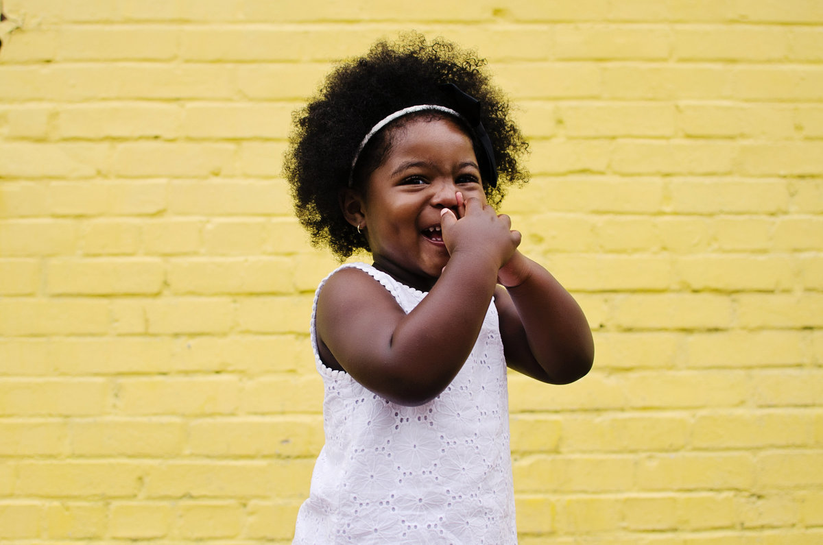Portrait of a little girl laughing against a yellow brick wall in Old Town Alexandria taken by Sarah Alice Photography