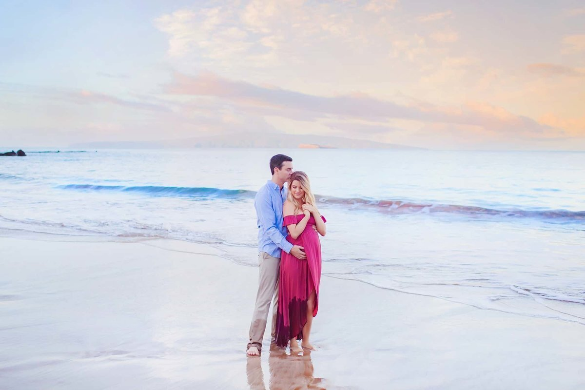 Couple and woman wearing a red maternity gown kiss during Maui portrait session
