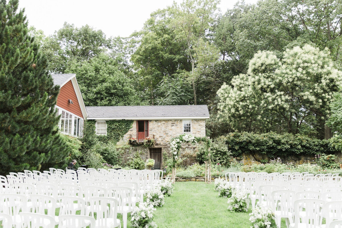 Wedding ceremony set up amidst estate gardens and historic buildings