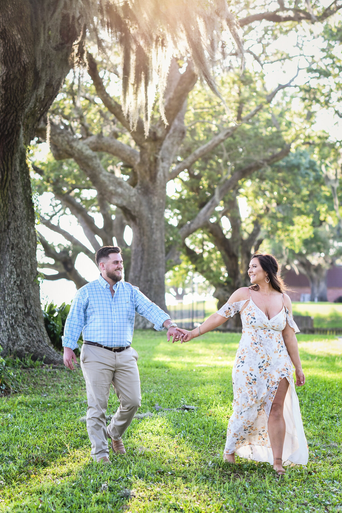 Beautiful Mississippi Engagement Photography: couple walks holding hands under oaks with spanish moss in Ocean Springs, MS
