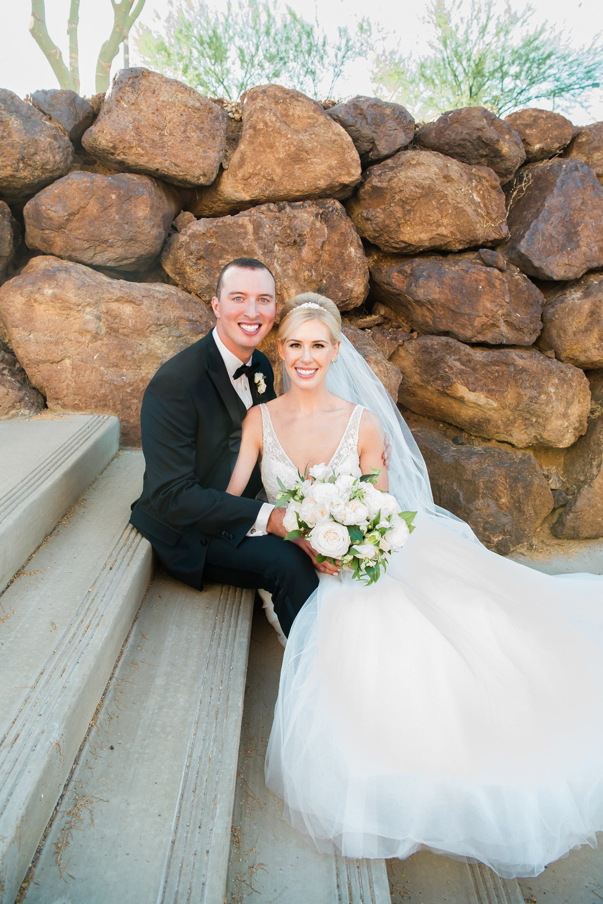a bride and groom sitting on the steps at Holy Spirit Catholic Church in Las Vegas